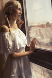 Beautiful woman with blond hair dreaming beside a window Stock Image