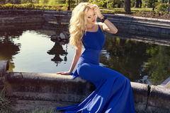 Beautiful woman with blond hair in elegant dress at park Stock Image