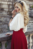 Beautiful woman with blond hair in elegant dress at park Stock Photos