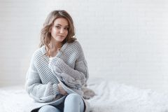 Beautiful woman with blond hair in a grey knitted sweater in a bright bedroom on a gray background. Winter Concept. Cute young girl in a gray knitted sweater Stock Photography