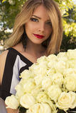Beautiful woman with blond hair holding roses Royalty Free Stock Images