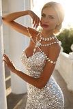 Beautiful woman with blond hair in luxurious dress and bijou Royalty Free Stock Images