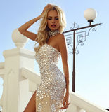 Beautiful woman with blond hair in luxurious dress and bijou Stock Photo