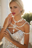 Beautiful woman with blond hair in luxurious dress and bijou Royalty Free Stock Photo
