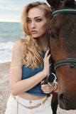 Beautiful woman with blond hair  posing with black horse Royalty Free Stock Image