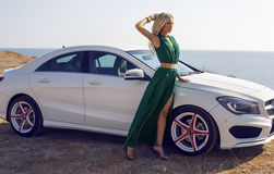 Beautiful woman with blond hair posing beside a luxury car Royalty Free Stock Photos