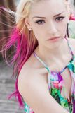 Beautiful Woman With Blond and Magenta Pink Hair. Outdoor portrait of a sad, moody or depressed, beautiful young woman or girl with brown eyes, blond and magenta Royalty Free Stock Photography