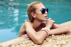 Beautiful woman with blond wet hair in aviator sunglasses Stock Photos