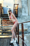 beautiful woman the blonde in bikini background an old ladde Royalty Free Stock Image