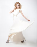 Beautiful woman blonde in flying vernal white dres. Sexy young lovely female blond hair with flying vernal dress  over white background Royalty Free Stock Photos