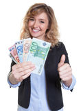 Beautiful woman with blonde hair and money showing thumb up Stock Photo