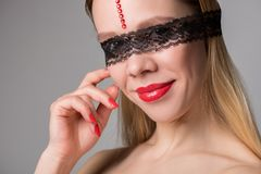 Beautiful woman blonde with lace on eyes over gray background royalty free stock photos
