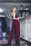Beautiful woman blonde model in a red jumpsuit a fashionable and Stock Photography