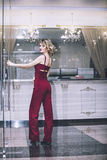 Beautiful woman blonde model in a red jumpsuit a fashionable and Stock Photos