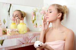 The beautiful woman blonde puts on face a cream royalty free stock photos