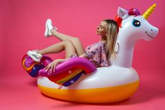 A beautiful woman blonde in a sexy sundress in white sneakers sits lifting her legs up on an inflatable multi-colored unicorn on a stock photography