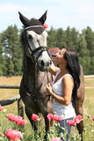 Beautiful woman in the blooming garden with horse Stock Images