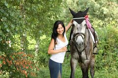 Beautiful woman in the blooming garden with horse Stock Photography