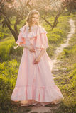 Beautiful woman in the blooming garden. Beautiful woman standing on the path through blooming garden in pink ball gown on sunset Stock Images