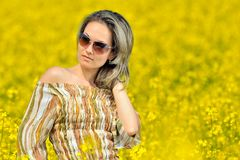 Beautiful woman on blooming rape field Royalty Free Stock Photo