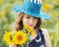 Beautiful woman on blooming sunflower field in summer Royalty Free Stock Image