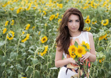 Beautiful woman on blooming sunflower field in summer Royalty Free Stock Photos