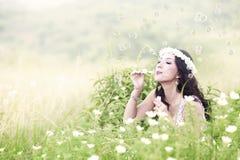 Beautiful woman blowing bubbles Stock Image