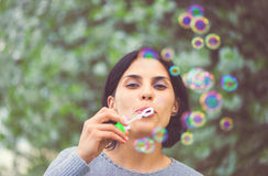 Beautiful woman blowing bubbles Royalty Free Stock Images