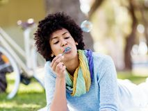 Beautiful woman blowing bubbles in park Royalty Free Stock Images