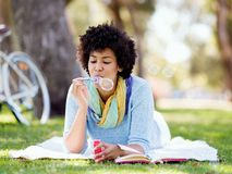 Beautiful woman blowing bubbles in park Stock Image