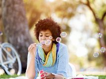 Beautiful woman blowing bubbles in park Stock Photo