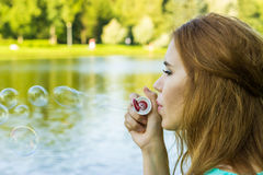 Beautiful woman blowing bubbles in the summe near the lake. Outdoors Stock Photo