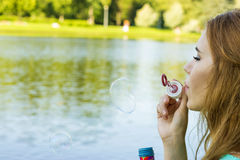 Beautiful woman blowing bubbles in the summer near the lake Stock Photos