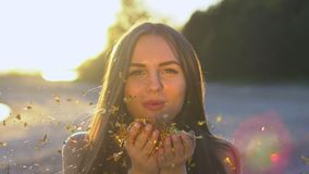 Beautiful woman blowing confetti in slow motion on the beach. Caucasian happy teenage girl blowing gold glitter off stock footage