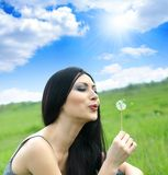 Beautiful woman blowing dandelion Royalty Free Stock Images
