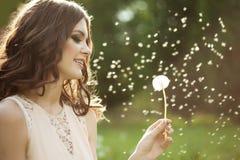 Beautiful woman blowing a dandelion Royalty Free Stock Image