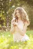 Beautiful woman blowing a dandelion Stock Photography