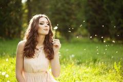 Beautiful woman blowing a dandelion. Beautiful young woman blowing a dandelion stock image