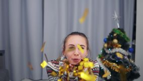 Beautiful woman blowing gold glitter confetti at home in slow motion. Beautiful young party woman blowing gold glitter. Confetti. Beauty brunette girl stock footage