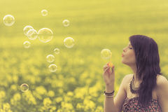 Beautiful woman blowing many soap bubbles in summer nature. The girl has fun in a yellow meadow and is enjoying her youth Stock Photo