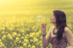 Beautiful woman blowing one soap bubble in yellow summer meadow. The girl has fun in nature and is enjoying her youth Stock Image