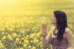 Beautiful woman blowing a single soap bubble in summer nature. The girl has fun in a yellow meadow and is enjoying her youth Stock Photo