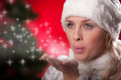 Beautiful woman blowing snow form hand. Beautiful woman in Christmas costume blowing snow form hand Stock Image