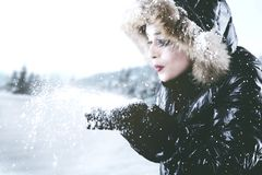 Beautiful woman blowing snow from hands. Beautiful young woman woman blowing snow from hands while wearing jacket on the park Stock Photo