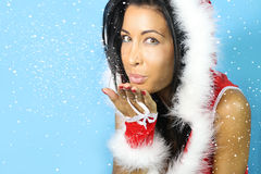Beautiful woman blowing snow. Beautiful young woman dressed santa blowing snow royalty free stock photography