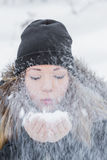Beautiful woman blowing snow Royalty Free Stock Photography