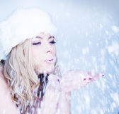Beautiful woman blowing snowflakes Royalty Free Stock Photo