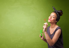 Beautiful woman blowing soap bubble on copyspace background Stock Image