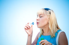 Beautiful woman blowing soap bubbles. Beautiful young woman blowing soap bubbles Stock Images