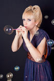 Beautiful woman blowing soap bubbles Royalty Free Stock Image